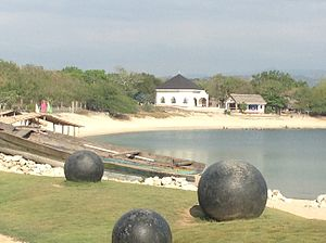 Sinait - The Chapel of the Santo Cristo Milagroso in Dadalaquiten Norte (the white building), taken from the Chapel of the La Virgen Milagrosa in nearby Paguetpet, Badoc.  The body of water in the picture is part of the seashore where the two images were allegedly found floating in a box.