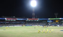 View of a cricket stadium. It has some players in yellow outfit and they are folding yellow flags.