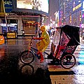 Cyclist riding passengers on a street in the rain at night in New York City, U.S.A.jpg