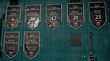 Seven large black shield-shaped banners are hung on a green wall, with white text for the name and number, or role that the individual played.