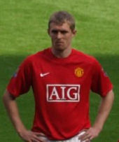 A white man with light hair standing with his hands on his hips. He is wearing a red football shirt.