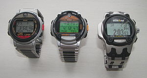 Timex Datalink - The evolution of the Datalink line shown with metal bands for easy comparison (left to right in order of chronological appearance): Datalink model 50 (1994), Ironman Triathlon, with the Ironman Triathlon logo on the upper part of the face (1997) and Datalink USB sports edition (2003). The small lens is seen on both model 50 and the Ironman. Note also the inverted circular arch digital display frame design on the model 50, compared to the frame design of the other two models. The Microsoft logo appears at the top, while the Datalink logo appears at the bottom for model 50. The lower button arrangement and platform is the same for both model 50 and Ironman triathlon, but Ironman sports an additional start/split button on its face, indicating its additional chronograph functions. All three models are water resistant to 100 m. The model 50 (Timex models 70502/70518) was worn by astronaut James H. Newman on STS-88.