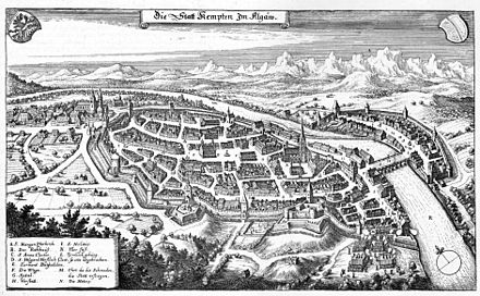 A finely detailed drawing of an old city, with church towers, thick defensive walls, moats, and lots of houses. The Iller river divided the Free Imperial City of Kempten and Kempten Abbey. De Merian Sueviae 144.jpg