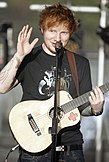 Ed Sheeran holding a guitar onstage while waving at the audience