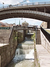 Original five step lock structure crossing the Niagara Escarpment at Lockport, now without gates and used as a cascade for excess water. A modern 40-foot-wide (12 meter) single-step lock is to the left, replacing another identical and original five-step lock.
