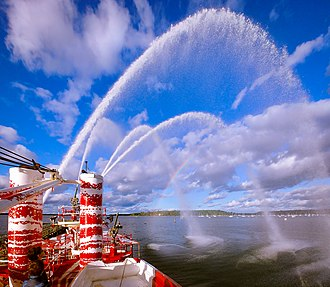 Fireboat - Onboard view of Fireboat John J. Harvey in Tauba Auerbach dazzle camouflage performing a water pumping demonstration in Oyster Bay, New York with artificial rainbow visible