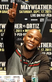 "Mayweather smiling and flashing ""V"" for victory with his right hand"
