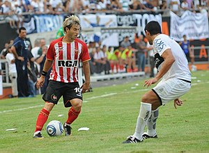 La Plata derby - Estudiantes striker Gastón Fernández carrying the ball followed by Ariel Agüero, during the derby played on 5 March 2011 in the Estadio Ciudad de La Plata in 2011.