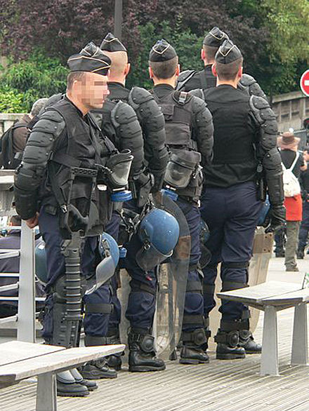 These gendarmes mobiles are ready for riot control; they carry gas masks and one has a grenade launcher for sending tear gas canisters Gendarmes mobiles p1200789.jpg