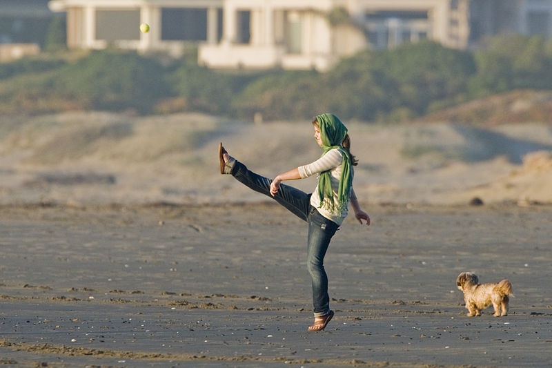 File:Girl kicking a ball playing on the sand beach in late light.jpg