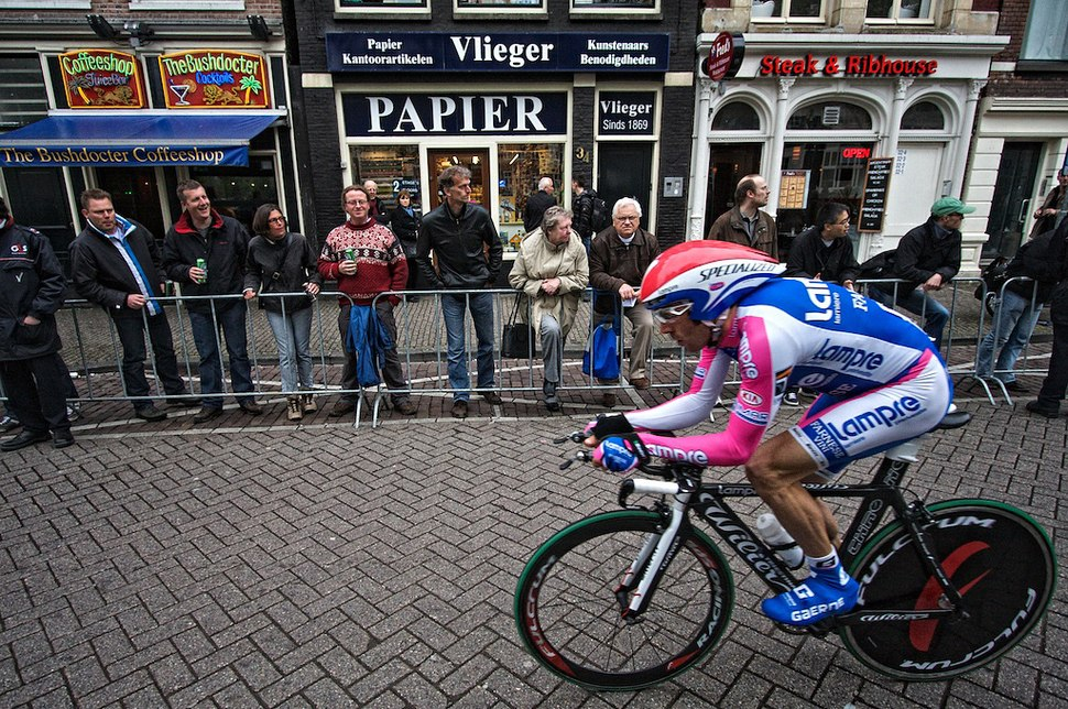 A man riding a bike while wearing a blue, white, and pink skinsuit.