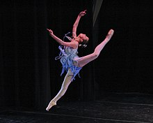 A contemporary ballet leap performed with modern, non-classical form