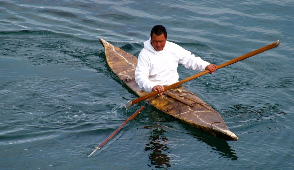 Man sitting with legs covered in boat that tapers to a point at each end holding long, pointed, wooden pole
