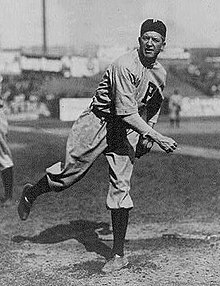 A pitcher finishing his delivery.  Pitcher appears to be throwing on the sidelines.