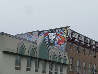 Guy Fawkes mask - Graffiti of a Guy Fawkes mask painted on the facade of a building overlooking the Chez Pops Day Centre for youths in Montreal, Quebec.