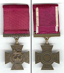 "The obverse and reverse of the bronze cross pattée medal; obverse showing the crown of Saint Edward surmounted by a lion with the inscription ""for valour"" with a crimson ribbon; the reverse shows the inscription of the recipient on the bar connecting the ribbon with the regiment in the centre of the medal."