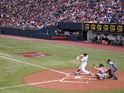 Joe Mauer swinging against Baltimore, catcher and umpire visible, in front of Metrodome crowd