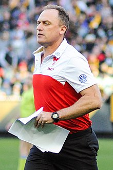 A dark-haired man in a red-and-white polo carrying papers