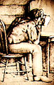 Smith sitting on a wooden chair with his face in a hat