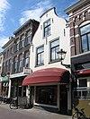 foto van Huis met geverfde in- en uitgezwenkte topgevel, siersteen en jongere winkelpui