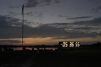 Launch Complex 39 Press Site - The flagpole and countdown clock at dawn before the STS-114 launch in July 2005