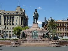Imponujący pomnik.  Na wysokim cokole stoi posąg Krugera;  on ma na sobie cylinder.  Obok każdego z czterech boków cokołu znajduje się posąg przyczajonego Boera.