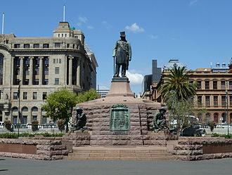 An impressive monument. A statue of Kruger stands on a tall plinth; he is wearing his top hat. Each of the plinth's four sides has a statue of a crouching Boer next to it.