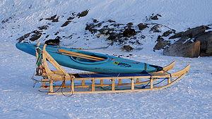 Qamutiik - A qamutit carrying a kayak, dogs asleep in background