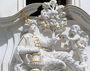 Relief of a young, cherub-like boy passing a cup to a reclining man with a moustache and hat. The sculpture is white with gold accents on the cup, clothes, and items.