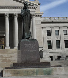 A statue of Abraham Lincoln in a robe, looking pensive
