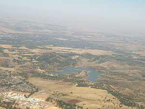 City of Playford - Looking northwest over Greenwith and the Little Para Reservoir from an aeroplane flying west down the River Torrens valley. The dark area on the far side of the reservoir is the suburbs of the City of Playford. In the background are the outer northern suburbs of Adelaide, and the northern Adelaide Plains of the Gawler River.