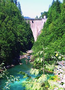 An arch dam straddles a narrow, forested canyon above a tumbling river