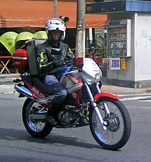 A firefighter in uniform, leather jacket and white helmet rides a motorcycle in red and white livery, equipped with emergency lights and a large pack of medical supplies, across a city street. Telephone booths and a newsstand are visible in the background.
