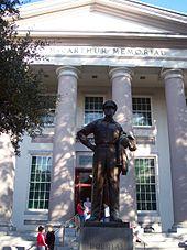 """Een groot bronzen beeld van MacArthur staat op een voetstuk voor een groot wit gebouw met zuilen.  Een inscriptie op het gebouw luidt: """"Douglas MacArthur Memorial""""."""