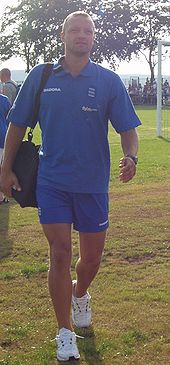 A muscular young white man wearing a blue sports shirt and shorts and carrying a kitbag walks across sunlit grass. In the background are trees and the edge of a football goal.