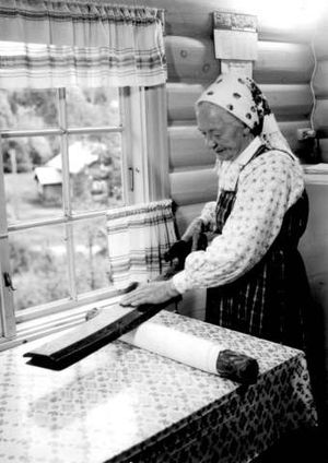 Mangle (machine) - With the dominant hand on the handle and the other hand on the mangle, the user presses on the roll while it is pushed back and forth. Photo: Norwegian Folk Museum 1962