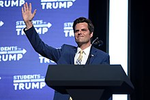"Gaetz waving in front of a lectern. ""Students for Trump"" logo emblazon the background."