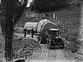 Medium distance shot of a Leyland truck transporting a piece of Kauri along a dirt road (AM 75777-1).jpg
