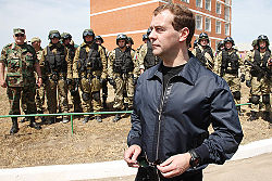Man in black in front of soldiers