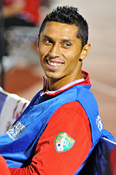 A young Latino man wearing a blue sleeveless T-shirt over a red long-sleeved T-shirt looks to his left and smiles.