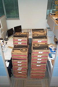 Boxes of monitors stacked in a cubicle.