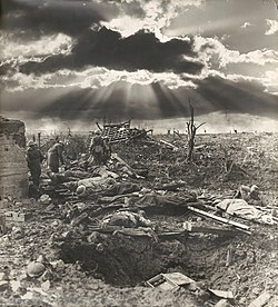 A sunburst through the clouds is shown against a landscape of destroyed land with a shell hole in the foreground.