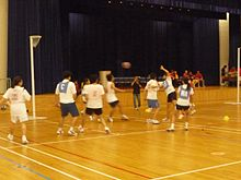 Short and t-shirt wearing players compete against each other.