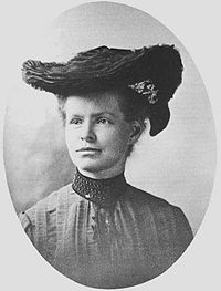 Black-and-white portrait photograph of Nettie Stevens in 1904 wearing a large black hat and formal attire