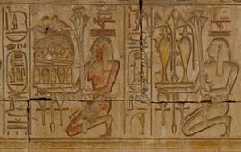 Relief showing two kneeling people carrying trays piled with plants, jars of liquid, and food.
