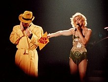 A man dressed as Dick Tracy in a yellow trenchcoat, with Madonna holding a manila envelope toward him and a microphone