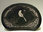An oval shaped pottery pillow with flat sides. It has an image of a white bird sitting on a branch.
