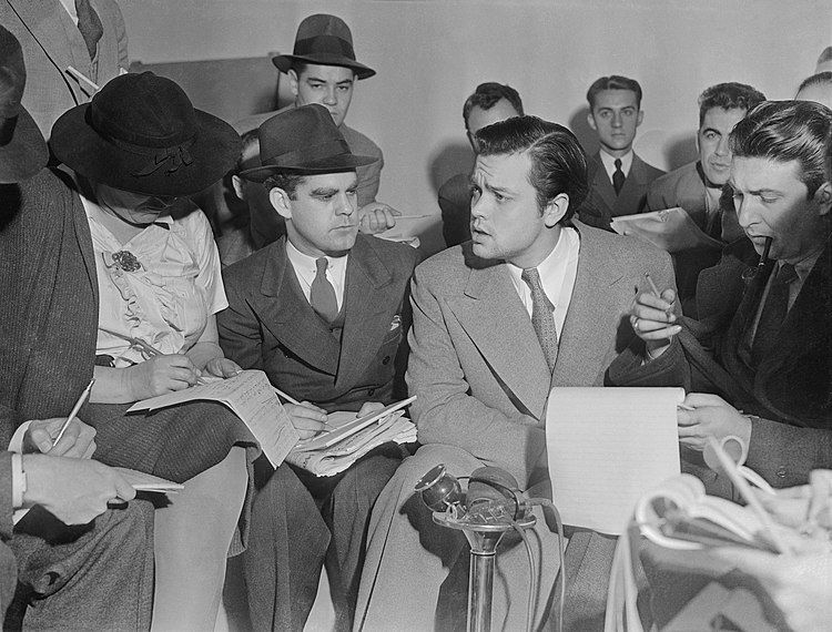 Photo of Orson Welles meeting with reporters in an effort to explain that no one connected with the War of the Worlds radio broadcast had any idea the show would cause panic