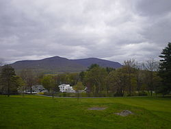 View of the south face of Overlook Mountain in Woodstock, NY with a white house in the foreground