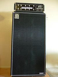 A tall, large speaker cabinet with a bass amplifier sitting on top. The speaker cabinet has eight ten-inch speakers.